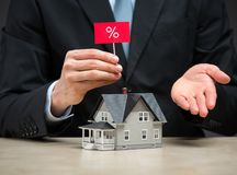 Feche acima de pouca casa e entregue o mantimento da tabuleta dos por cento Foto de Stock Royalty Free