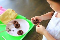 Feche acima de pouca menina asiática da criança na classe do processo de anéis de espuma caseiros do chocolate imagens de stock
