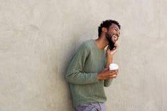 Feche acima de rir o homem africano que guarda o café e o telefone esperto imagem de stock royalty free