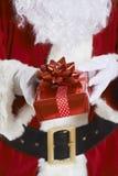 Feche acima de Santa Claus Holding Gift Wrapped Present imagem de stock