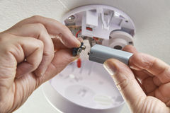 Feche acima de substituir a bateria no alarme de fumo doméstico foto de stock