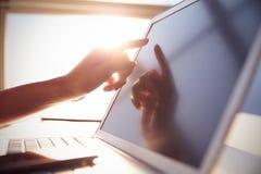 Feche acima de tela tocante do portátil da mão com alargamento da lente foto de stock royalty free