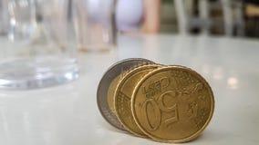 Feche acima de três moedas do Euro que estão na tabela lustrosa branca fotografia de stock