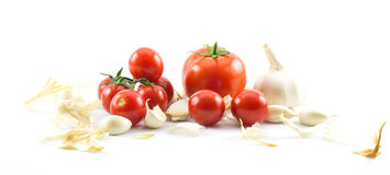 Feche acima de três tipos dos tomates - vermelho grande, por muito tempo e cereja e alho em um fundo branco Imagem de Stock Royalty Free