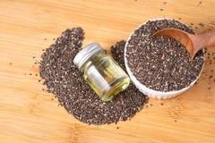 Feche acima de um óleo essencial e das sementes de Chia na colher, no superfood e em ricos de madeira do nutriente um antioxidant imagem de stock