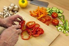 Feche acima de um anel das mãos dos cozinheiros chefe que corta uma pimenta de sino vermelha Fotos de Stock Royalty Free