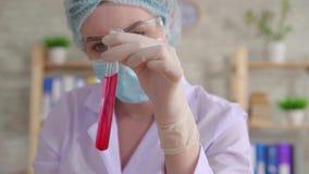 Feche acima de um assistente de laboratório da mulher que conduz um estudo do líquido em um tubo de ensaio mo lento video estoque