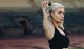 Feche acima de um atleta fêmea que faz para aquecer exercícios imagem de stock
