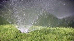 Feche acima de um bocal de um bocal para pulverizar da água do sistema de molhar automático de um gramado com brilhantemente o ve vídeos de arquivo