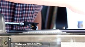 Feche acima de um braço da plataforma giratória com um registro de vinil que dobra-se com o calor do Sun filme