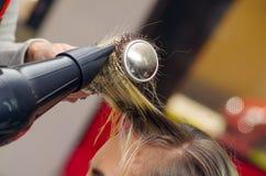 Feche acima de um cabeleireiro que seca o cabelo louro com secador de cabelo e a escova redonda em um fundo borrado imagens de stock royalty free
