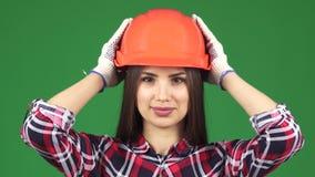 Feche acima de um capacete de segurança vestindo de sorriso do constructionist fêmea bonito 'sexy' filme