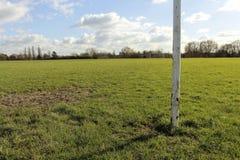 Feche acima de um cargo do objetivo em um campo em The Sun Fotos de Stock