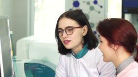 Feche acima de um cientista fêmea bonito que fala a seu colega video estoque
