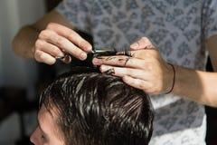 Feche acima de um corte de cabelo no bar do cabelo Barbeiro que triming o cabelo de um cliente com tesouras foto de stock royalty free