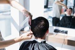 Feche acima de um corte de cabelo no bar do cabelo Barbeiro que triming o cabelo de um cliente com tesouras fotografia de stock