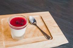 Feche acima de um cotta saboroso do panna com xarope vermelho no prato de madeira fotografia de stock royalty free