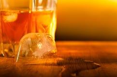 Feche acima de um cubo de gelo que derrete com uma bebida Fotografia de Stock
