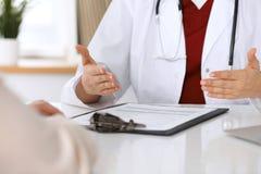 Feche acima de um doutor e das mãos do paciente ao discutir informes médicos após o exame da saúde Fotografia de Stock