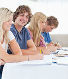 Feche acima de um estudante de sorriso com os amigos que olham a câmera Imagem de Stock Royalty Free
