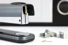Feche acima de um grampeador com grampos fotografia de stock