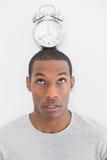 Feche acima de um homem com um despertador sobre sua cabeça Fotografia de Stock Royalty Free
