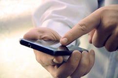 Feche acima de um homem de negócios usando o telefone esperto imagem de stock royalty free