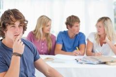 Feche acima de um homem de pensamento que senta-se na frente de seus amigos Fotografia de Stock