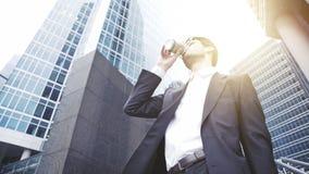 Feche acima de um homem de negócios novo nos vidros que bebe o café em uma baixa Fotos de Stock