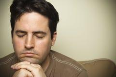 Feche acima de um homem novo na oração Imagens de Stock Royalty Free