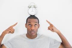 Feche acima de um homem que aponta no despertador sobre sua cabeça Foto de Stock Royalty Free