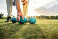 Feche acima de um homem que escolhe uma posição dos boules em um gramado foto de stock royalty free