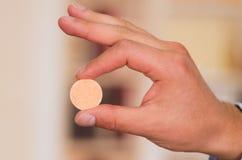 Feche acima de um homem que guarda uma tabuleta efervescente em sua mão com fundo borrado Fotografia de Stock Royalty Free