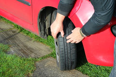 Feche acima de um homem que inspeciona pneus ou pneumáticos de carro. Imagens de Stock Royalty Free