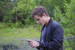 Feche acima de um homem que usa o telefone esperto móvel Foto de Stock Royalty Free