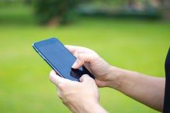 Feche acima de um homem que usa o telefone esperto móvel no parque mãos a imagens de stock