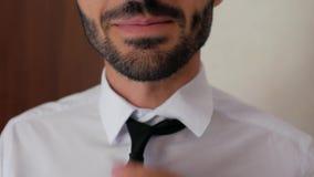 Feche acima de um indivíduo com uma barba em uma camisa branca está amarrando um laço e endireita-o o homem endireita o colar da  filme