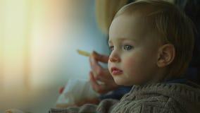 Feche acima de um menino pequeno bonito que come batatas fritas foto de stock royalty free