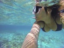 Feche acima de um mergulho autônomo da jovem mulher em um mar transparente Fotos de Stock