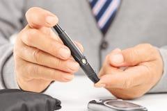 Feche acima de um nível de medição maduro do açúcar no sangue usando o glucom Fotografia de Stock Royalty Free