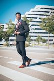 Feche acima de um novo e do homem de negócios preto atrativo que atravessa um cruzamento pedestre e que fala pelo telefone na fre fotos de stock