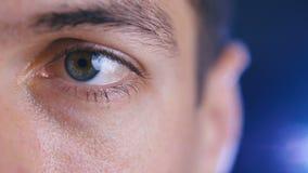 Feche acima de um olho masculino Detalhe de um olho de um homem que olha a câmera Tiro macro vídeos de arquivo