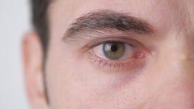 Feche acima de um olho masculino do ` s O aluno reduz no movimento lento video estoque