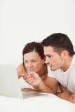 Feche acima de um par feliz com um portátil Imagem de Stock Royalty Free