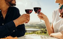 Feche acima de um par que brinda o vinho fotografia de stock royalty free