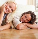 Feche acima de um par que encontra-se no assoalho Fotos de Stock Royalty Free