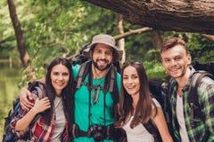 Feche acima de um retrato colhido de quatro amigos alegres na madeira agradável do verão São caminhantes, andando e escolhendo o  imagens de stock royalty free
