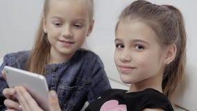 Feche acima de um retrato de duas meninas de sorriso que encontram-se no sofá e que usam a tabuleta, estudantes pequenos consider filme