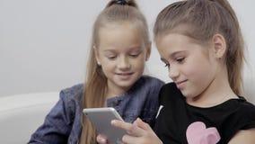 Feche acima de um retrato de duas meninas de sorriso que encontram-se no sofá e que usam a tabuleta, estudantes pequenos consider vídeos de arquivo
