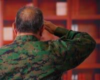 Feche acima de um soldado de veterano sério que veste um uniforme militar, fazendo um sinal dos cumprimentos à autoridade com o s fotografia de stock